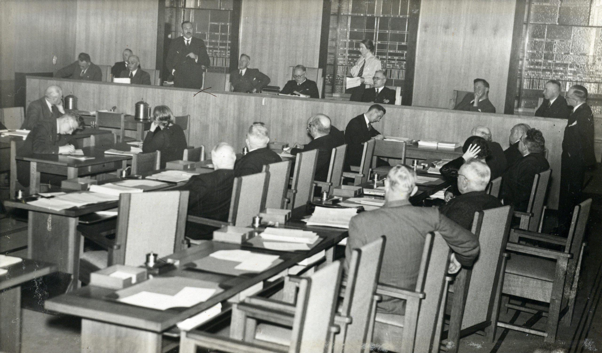 1938: Afbeelding van een vergadering van de gemeenteraad in de raadzaal van het Stadhuis (Stadhuisbrug 1) te Utrecht. N.B. In deze vergadering werd o.a. het besluit genomen tot vaststelling van het uitbreidingsplan van het gebied ten oosten van de Willem Barentszstraat ((flat)woningbouw aan de Karel Doormanlaan).